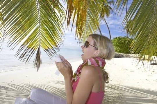 Frau mit Schnupfen am Strand