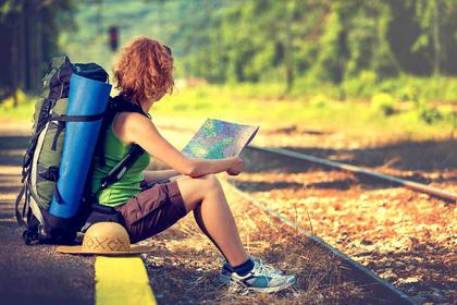 Frau sitzt auf Bahnsteig mit Landkarte