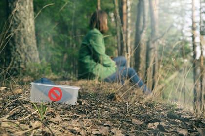 Frau sitzt im Wald. Das Handy liegt in einer Box