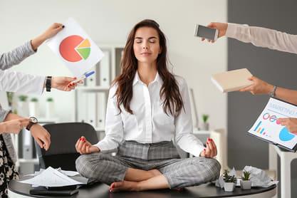 Frau sitzt auf Tisch und viele Hände bedrängen sie mit Büroartikel