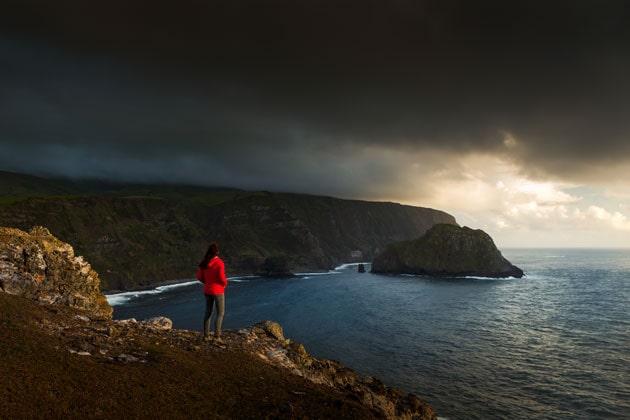 ein Mensch steht an einer Felsklippe und blickt bei einem Gewitter auf das Meer