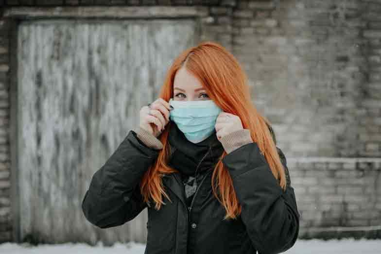 Frau setzt sich Maske auf Corona Reiserücktritt Reiseabbruch Versicherung Reiseversicherung Covid-19 Ansteckung vermeiden beim Bahnfahren Zugfahren