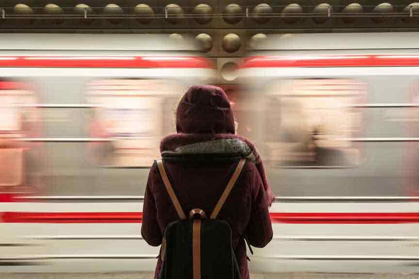 Frau vorbeifahrender Zug Corona Reiserücktritt Reiseabbruch Versicherung Reiseversicherung Covid-19 Ansteckung vermeiden beim Bahnfahren Zugfahren