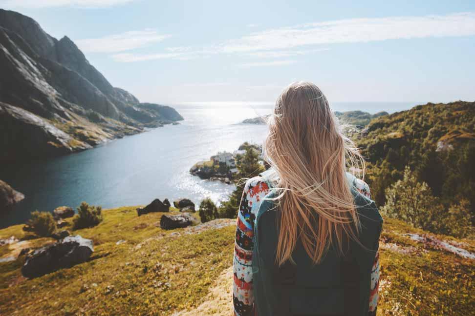 Frau mit blonden Haaren sitzt auf einem Berg und blickt auf einen See