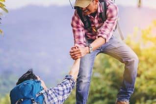 Wanderer reicht anderem Wanderer die Hand, um ihn zu retten