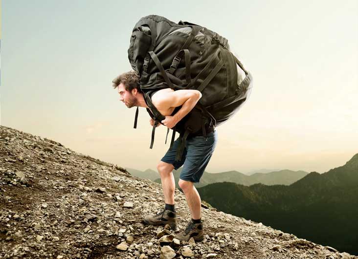 Mann trägt schwer beladenen Wanderrucksack auf dem Rücken einen Berg hoch