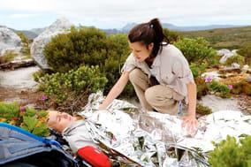 Rettungsassistentin versorgt verunglückten Wanderer in steinigem Gelände