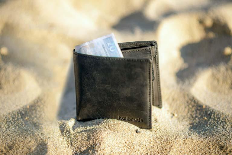 Geldbeutel im Sand Reise Urlaub buchen Corona kein finanzielles Risiko Reiseruecktritt Reiseabbruch Versicherung Covid-19