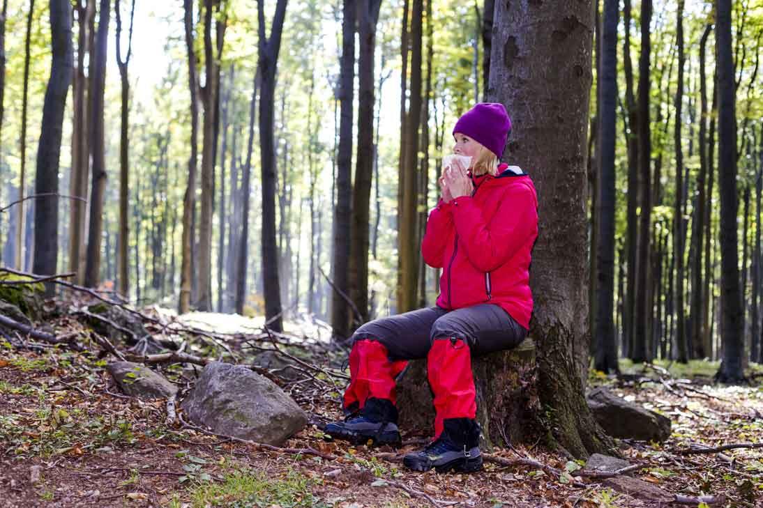 Frau mit roter Jacke und Hose sitzt im Wald und putzt sich die Nase