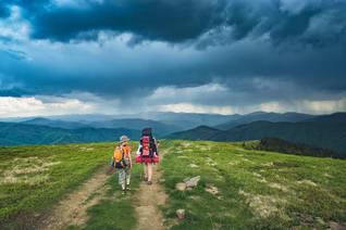 zwei Menschen wandern auf einem Wanderweg in den Bergen und ein Gewitter zieht auf