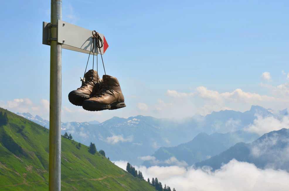 Wanderschuhe hängen auf Wanderwegweiser