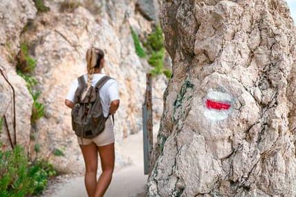 Frau wandert mit kurzer Hose einen Bergwanderweg entlang